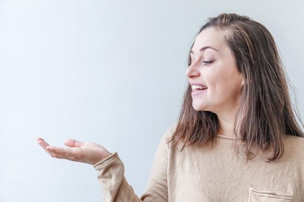 Счастливая девушка улыбается веселая. женщина брюнет портрета красоты молодая счастливая положительная смеясь над представляя и указывая показывая открытую руку ладони на белой изолированной предпосылке.
