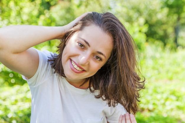 야외에서 웃 고 행복 한 소녀입니다. 공원이나 정원의 녹색 배경에서 쉬고 있는 아름다운 젊은 brunete 여자