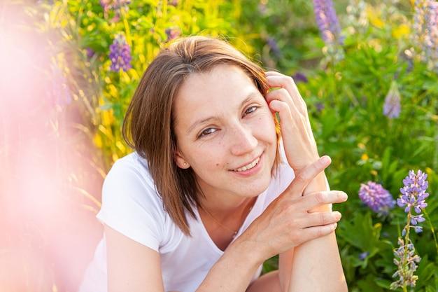 야외에서 웃 고 행복 한 소녀입니다. 아름 다운 젊은 brunete 여자 개화 야생 꽃 녹색 배경으로 여름 필드에 휴식. 무료 행복 유럽 여자입니다. 긍정적인 인간의 감정 표정.