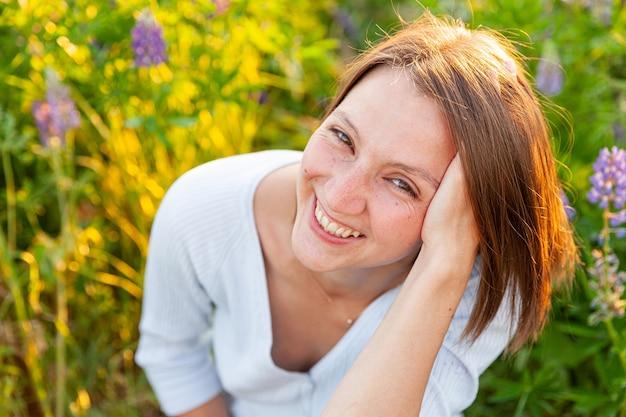 屋外で笑って幸せな女の子。咲く野生の花と夏のフィールドで休んでいる美しい若いブルネットの女性。無料の幸せなヨーロッパの女性。ポジティブな人間の感情の表情。