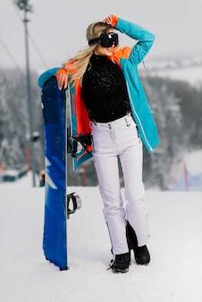 スノーボードとサングラスでポーズをとって幸せな女の子スノーボーダー