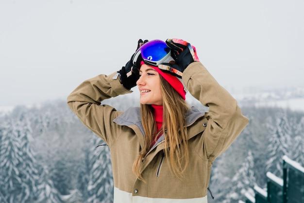 Счастливая девушка сноубордист позирует в солнцезащитных очках со сноубордом