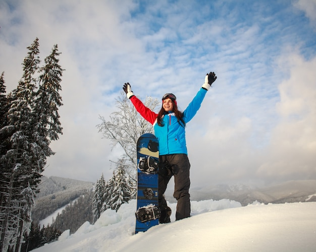 Happy girl snowboarder in snow winter stands on top of a mountain