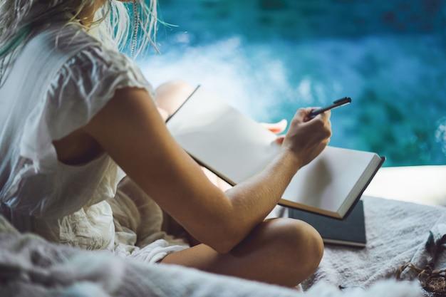 행복한 여자는 아늑한 인테리어에 집에서 시간을 보내고, 노트북에 쓰고 그립니다.
