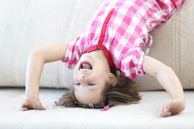 행복 한 여자는 소파에 그녀의 머리에 서 서. 집에서 아이 재미있는 게임