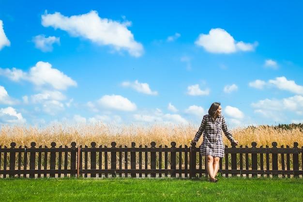 幸せな女の子は青い雲の空の下の緑のフィールドに木製のフェンスで立っています。美しい風景