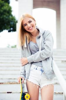 Счастливая девушка, стоящая на лестнице со скейтбордом