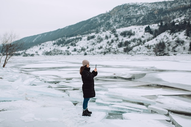 Happy girl standing on a shore of river in the winter and taking photo on the phone. girl enjoying the view of the frozen river.