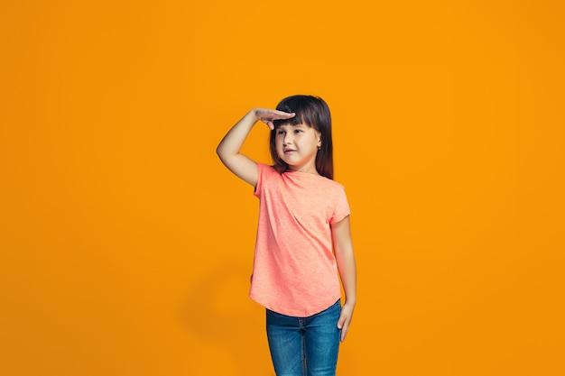 La ragazza felice che sta e che sorride contro la parete arancio