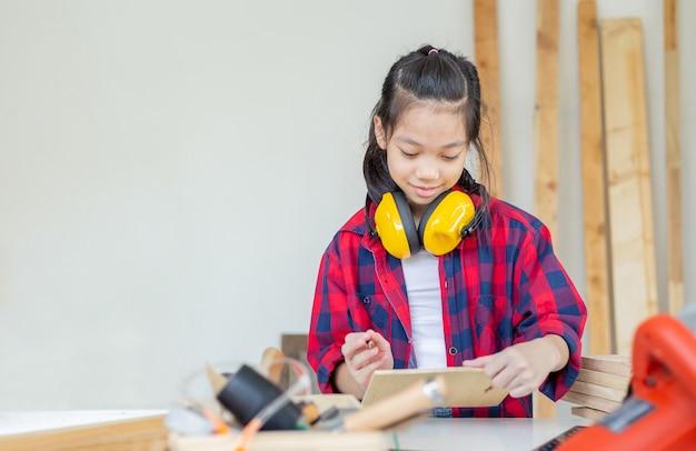 大工のワークショップでノイズリダクションイヤーマフで立っている幸せな女の子。職人工房で学ぶ子どもたち