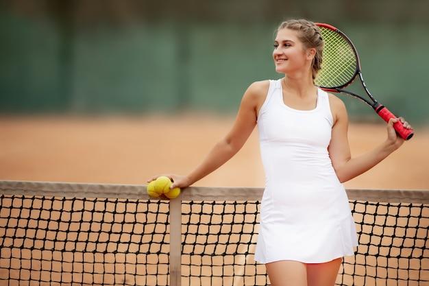 ネットの近くのコートにラケットとテニスボールを持って立って、目をそらしている幸せな女の子