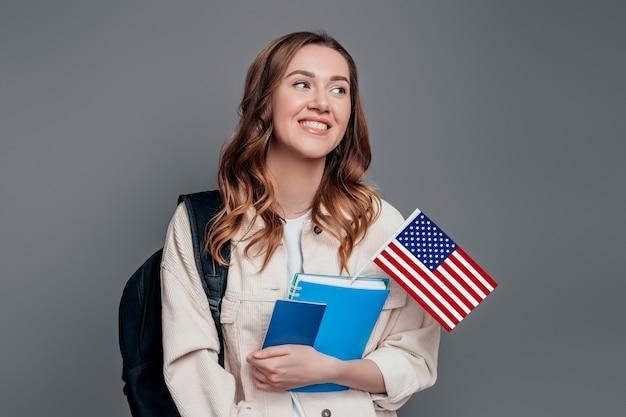 バックパック本ノートパスポートと暗い灰色の壁に分離された米国旗を保持している幸せな女子生徒