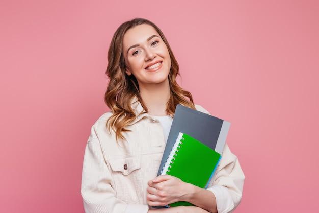 노트북 메모장을 들고 밝은 옷을 입고 행복 한 여자 학생 웃 고 텍스트 분홍색 벽에 카메라를 찾고 그녀의 손에 폴더