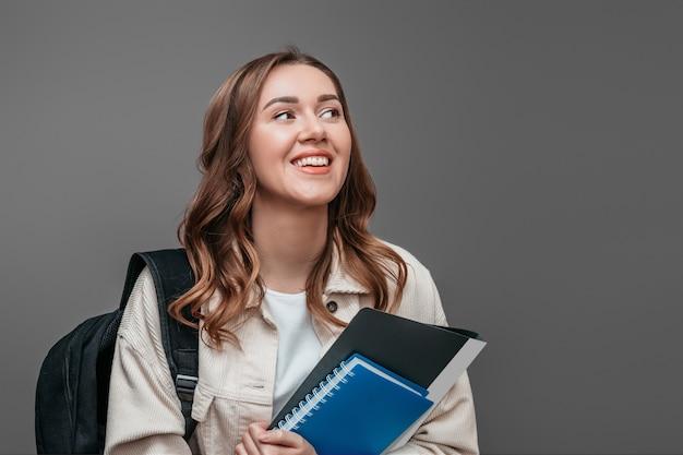 幸せな女子学生は笑って、笑顔と暗い灰色の壁に分離されたノートを保持しているよそ見。大学入試のコンセプト