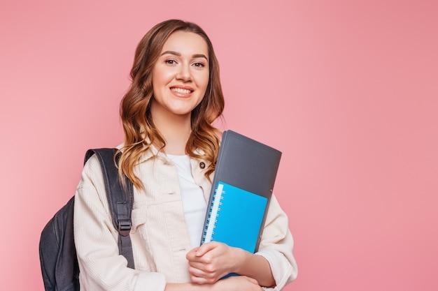 バックパックと幸せな女子生徒は笑顔し、ピンクの壁で隔離の手でノートのコピーブックフォルダーを保持しています。教育研究試験の概念は英語を学ぶ