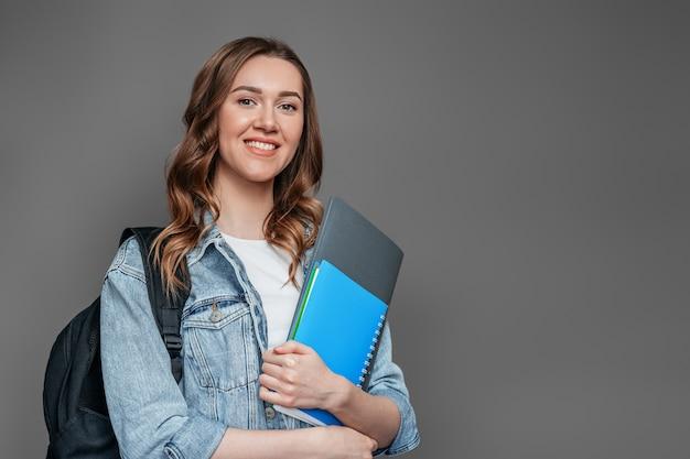 バックパックと幸せな女子生徒は笑顔し、暗い灰色の壁に分離された手でノートのコピーブックフォルダーを保持しています。教育研究試験の概念は英語を学ぶ