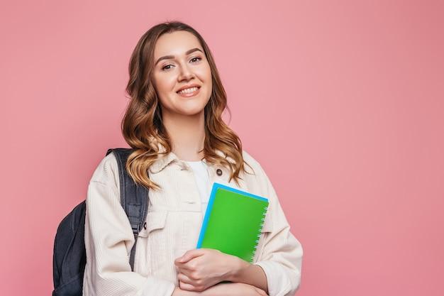 バックパックと幸せな女子生徒は笑顔し、ピンクの壁のwebバナーに分離されたノートを保持しています。教育の概念は英語を学ぶ