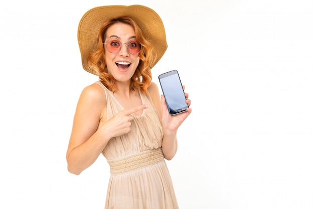 Happy girl in a summer hat and sunglasses holds a phone with a mockup on a white background