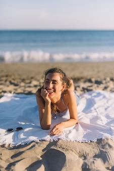 Ragazza felice prendere il sole sulla spiaggia
