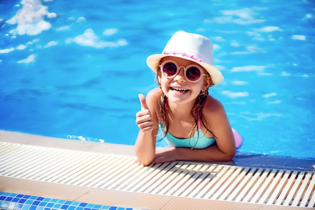Happy girl in sunglasses and hat with unicorn show thumb up in outdoor swimming pool of luxury resort on summer vacation on tropical beach island
