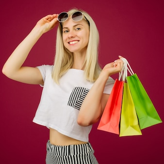 Happy girl in sunglasses holds shopping bags