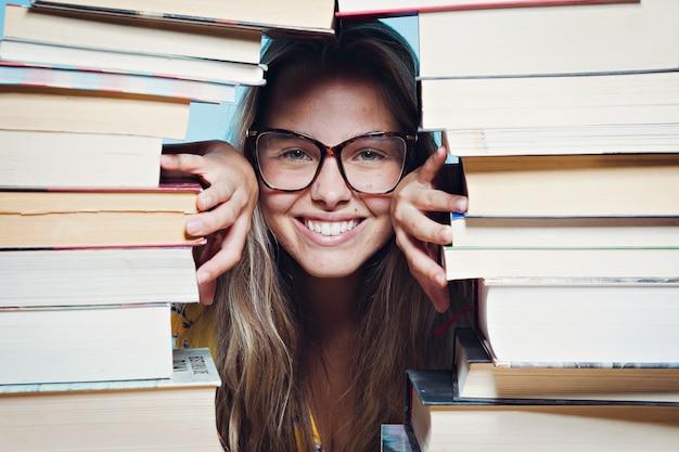 Счастливая девушка в окружении книг
