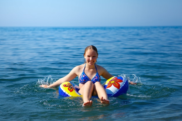 Happy girl swims in the sea on a circle.