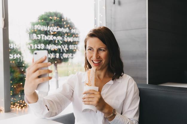 Счастливая девушка делает селфи на мобильном телефоне, пока ест твистер в кафе.