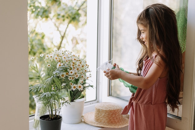 Happy girl taking care of houseplants at home dressed in stylish dusty pink outfit home gardening