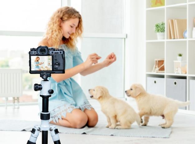 子犬に家に座るように教える幸せな女の子