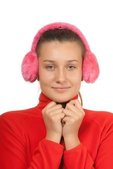 白で隔離されるピンクのヘッドフォンで十代の幸せな女の子