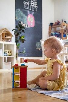 행복한 소녀 유아가 색깔 있는 공에 나무 망치를 치는 초기 개발 생태 장난감