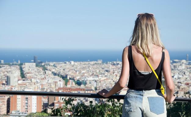 Счастливая девушка турист в барселоне с парком гуэль на фоне. задний взгляд молодой женщины наслаждаясь городом барселоны. молодая девушка турист, глядя на панорамный вид на город барселона. испания.
