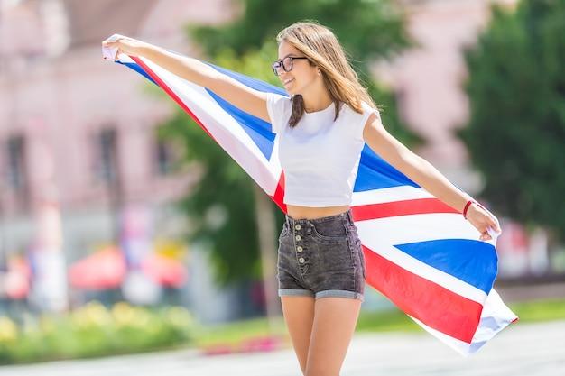 Счастливая туристическая девушка, идущая по улице с флагом великобритании.