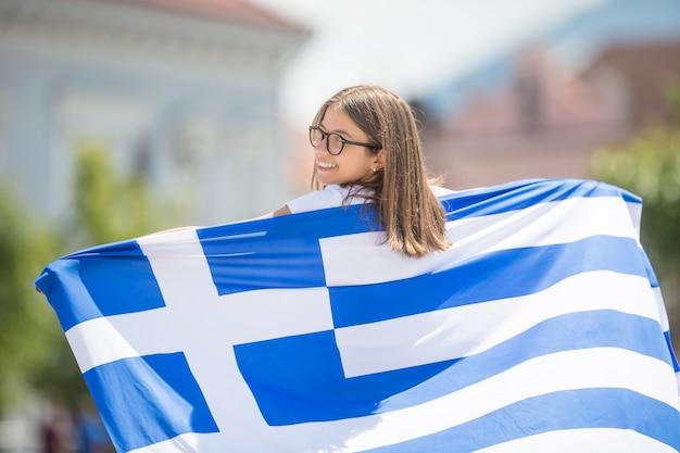 ギリシャの旗と通りを歩いて幸せな女の子の観光客。