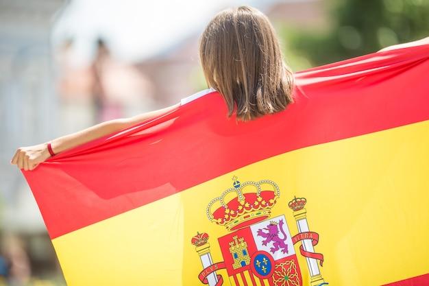 Счастливая туристическая девушка, идущая по улице с испанским флагом.