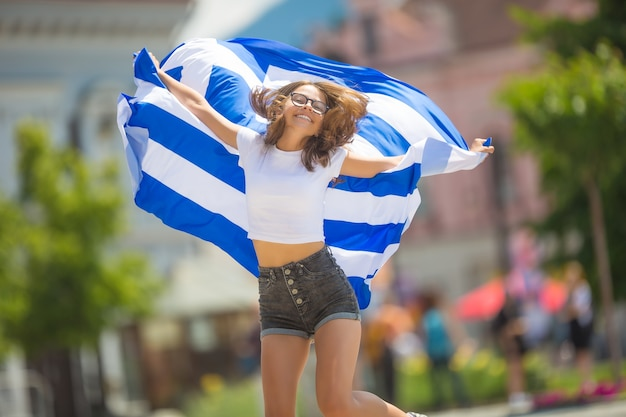 Happy girl tourist walking in the street with greece flag.