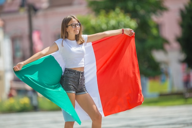 Happy girl tourist walking in the street with italian flag.