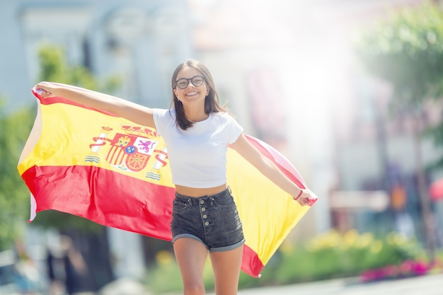 Happy girl tourist walking in the street with spanish flag.