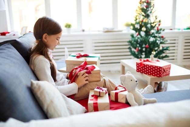 Счастливая девушка разворачивает рождественские подарки