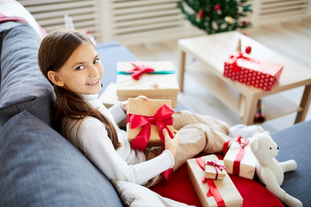 Happy girl unwrapping christmas presents