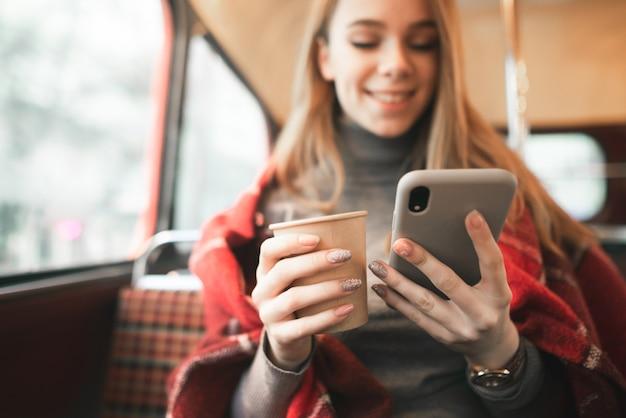 Счастливая девушка использует смартфон и пьет кофе в уютном кафе