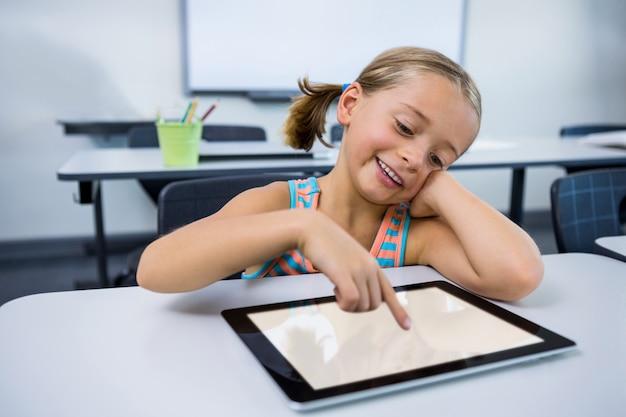 教室でデジタルタブレットを使用して幸せな女の子