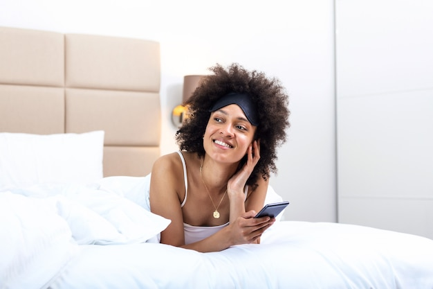 Happy girl using a mobile phone lying on the bed at home. beautiful young smiling woman lying in her bed with sleeping eye mask and using a phone in her bedroom.