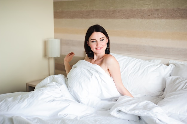 Счастливая девушка просыпается протягивать руки на кровати в первой половине дня.