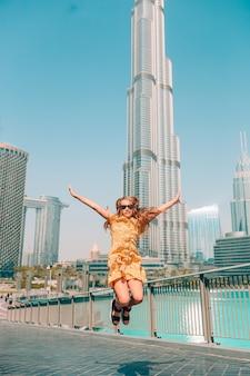 Happy girl walking in dubai with skyscraper in the background.