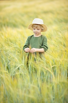 Happy girl walking in golden wheat, enjoying the life in the field. nature beauty and field of wheat. family outdoor lifestyle. freedom concept. cute little girl in summer field