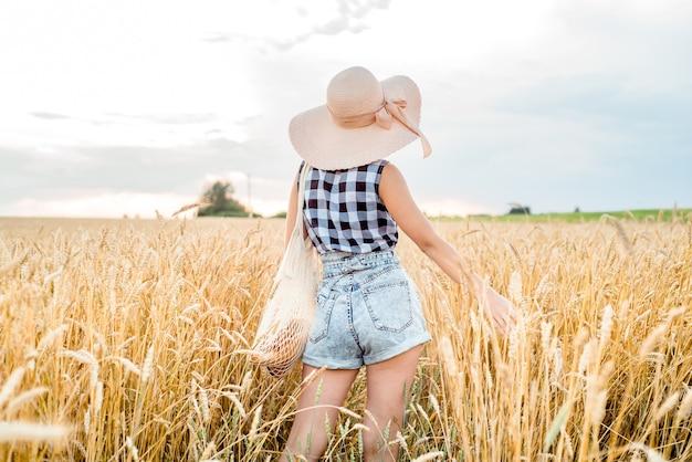 黄金の小麦の中を歩いている幸せな女の子、彼女の背中、アウトドアライフスタイル。自由の概念。