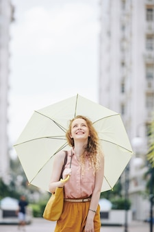 Happy girl walking with umbrella