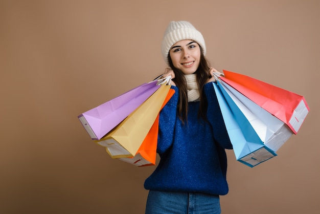 Happy girl in warm clothes with shopping bags, season of big discounts, copy space